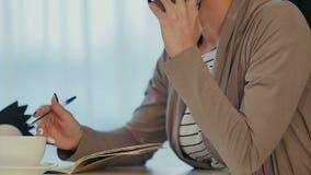 Affärskvinna som talar på telefonen och gör anmärkningar i ett kafé under kaffeavbrott lager videofilmer