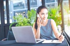 Affärskvinna som talar på telefonen och in skriver på en anteckningsbok Arkivbild