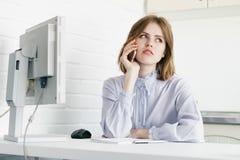 Affärskvinna som talar på telefonen på skrivbordet En i kontoret i vindstilen Royaltyfri Fotografi