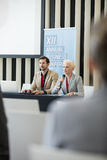 Affärskvinna som talar till och med mikrofonen, medan sitta med kollegan i seminariumkorridor Royaltyfri Fotografi
