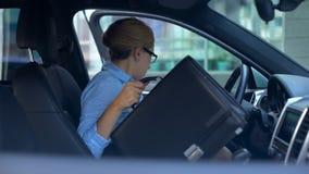 Affärskvinna som tar portföljen och får ut ur bilen som parkeras nära kontorsmitt royaltyfri bild