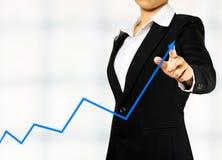 Affärskvinna som tecknar en graf Arkivfoton