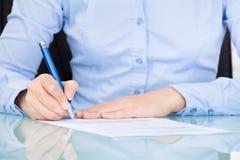 Affärskvinna som undertecknar på papper Fotografering för Bildbyråer
