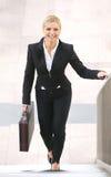 Affärskvinna som uppför trappan ler och går med portföljen Royaltyfria Foton