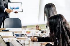 Affärskvinna som uppmärksamt lyssnar till en affärsman arkivfoto