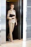 Affärskvinna som ut går hissen Royaltyfri Fotografi