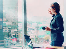 Affärskvinna som ut ser fönstret royaltyfri bild