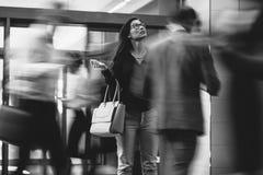 Affärskvinna som väntar på någon i en upptagen lobby royaltyfria foton