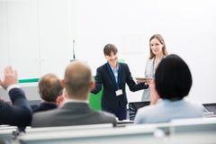 Affärskvinna Standing By Colleague, medan ge presentation till arkivfoto