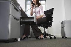 Affärskvinna Talking On Telephone, medan öppna enheten i Offic Arkivfoto