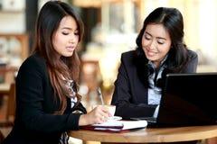 Affärskvinna två diskuterar viktiga diagram över deras cof Arkivbild