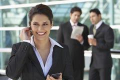 Affärskvinna Using Cell Phone utanför kontor Royaltyfria Bilder
