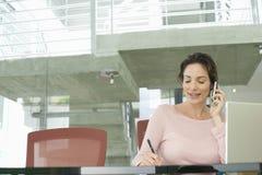 Affärskvinna Using Mobile Phone, medan skriva på notepaden royaltyfri foto