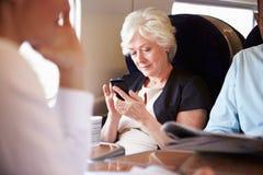 Affärskvinna Using Mobile Phone på den upptagna pendeltåget Fotografering för Bildbyråer