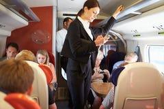 Affärskvinna Using Mobile Phone på den upptagna pendeltåget royaltyfria bilder