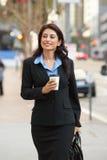 Affärskvinna Walking Along Street som rymmer Takeaway kaffe Royaltyfri Foto