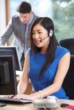 Affärskvinna Wearing Headset Working i upptaget kontor royaltyfri foto