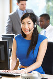 Affärskvinna Wearing Headset Working i upptaget kontor arkivbild