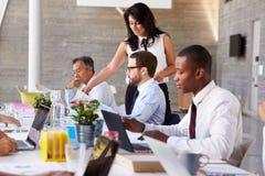 Affärskvinna Working With Colleagues på styrelsetabellen arkivbilder