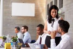 Affärskvinna Working With Colleagues på styrelsetabellen arkivfoto