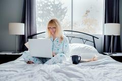 Affärskvinna Working i säng Arkivfoton