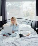 Affärskvinna Working i säng Royaltyfri Fotografi