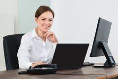 Affärskvinna Working On Laptop och skrivbords- dator Fotografering för Bildbyråer