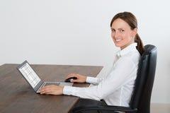 Affärskvinna Working On Laptop på skrivbordet Arkivbilder