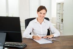 Affärskvinna Writing On Document Royaltyfria Bilder