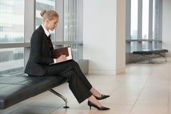 Affärskvinna Writing In Planner på kontorslobbyen royaltyfria foton