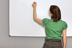 Affärskvinna Writing On Whiteboard i regeringsställning royaltyfri foto