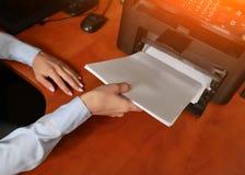 Affärskvinnaaffärsmannen satte pappersarket in i skrivarmagasinet arkivfoto