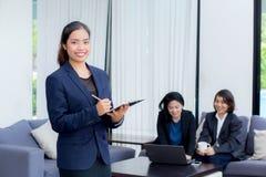 affärskvinnaanseende med anteckningsboken med kollegor i lag Arkivbilder