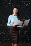 Affärskvinnaanseende och hållande bärbar dator, främre sikt Vindtegelstenvägg på bakgrund Begrepp av arbete Arkivbild