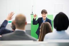 AffärskvinnaAsking Questions To kollegor, medan ge presentation arkivfoto