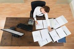 AffärskvinnaAttending Call While beräknande finans arkivfoton