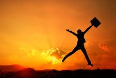 Affärskvinnabanhoppning och solnedgångsilhouette arkivfoto