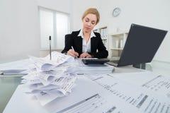 AffärskvinnaCalculating Invoice At skrivbord arkivbild
