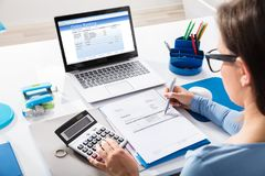 AffärskvinnaCalculating Invoice Using räknemaskin royaltyfri bild
