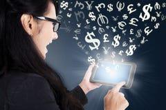 Affärskvinnadanandepengar direktanslutet med minnestavlan Royaltyfri Bild