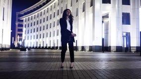 Affärskvinnadans och sjunga med en smartphone i en nattgata lager videofilmer