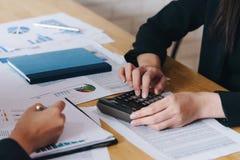 Affärskvinnadiskussion diagrammen och graferna som visar resultaten av deras lyckat Redovisa, finanser och ekonomibegrepp arkivbilder