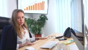 Affärskvinnadricksvatten på hennes skrivbord i hennes kontor arkivfilmer