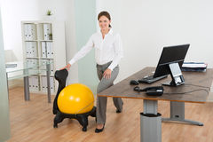 AffärskvinnaExercising With Pilates boll på stol Royaltyfria Bilder