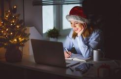 Affärskvinnafreelanceren tröttade och att arbeta på datoren på jul royaltyfri foto