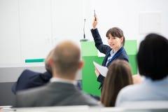 AffärskvinnaGiving Presentation To kollegor i seminariet Hall Arkivbild