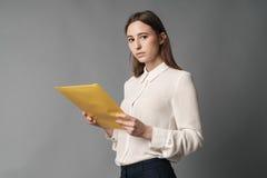 Affärskvinnahålldokument i henne hand en Isolerat på grå bakgrund Arkivbild