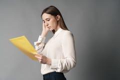 Affärskvinnahålldokument i henne hand en Isolerat på grå bakgrund Royaltyfri Foto
