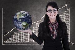 Affärskvinnahålljordklot på den växande svart tavlan för stångdiagram Arkivfoto