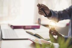 Affärskvinnahand som rymmer den ljusa kulan med ljusa kulor Royaltyfria Bilder